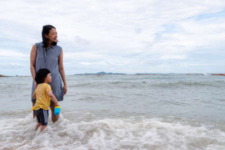 Mother and 3 years old asian kid playing on the beach. Background for family vacation and recreation. Stock fotó