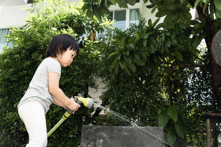 Funny moment of 3 Year old asian kid playing water with garden hose in backyard. Background concept  for play time and summer of children.