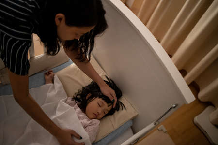 Mother checks the temperature of her kid. Concept for health and take care of children. 版權商用圖片
