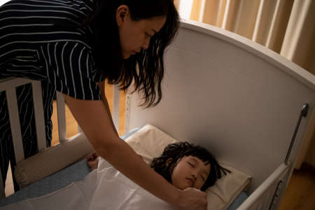 Close up asian mother tuck the blanket on kid sleep in bed. Concept for family connection and relationship.