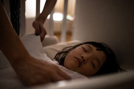 Close up asian mother tuck the blanket on kid sleep in bed. Concept for family connection and relationship. 版權商用圖片 - 164462874