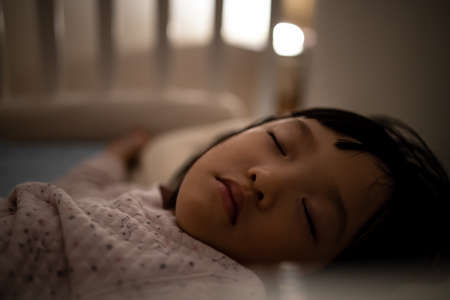 Close up asian face kid sleep in bed. Concept for resting and relaxation time of family.