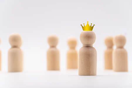 The crown icon on one wooden human icon . Concept for the winner of competition. Stock fotó