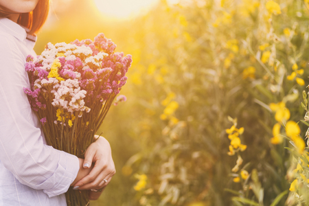arm bouquet: Lady, hands holding a bouquet of statice flowers, soft, spring sunset Stock Photo