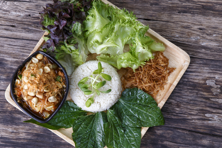 Asian food. Rice mixed with Coconut Cream With Papaya Salad (khao Man Som Tam) on wooden background