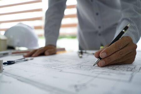 Mani dell'architetto che lavorano su piani di progetto con una matita, un righello, una calcolatrice, uno smartphone, un laptop e strumenti di ingegneria