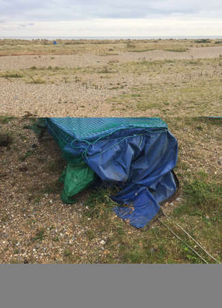 Small fishing boat in storage, covered with a cloth on a quiet beach in East Anglia