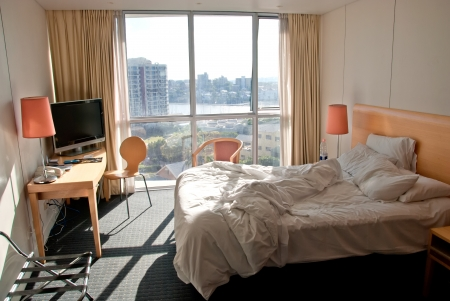 Hotel Bedroom with Unmade Bed and City View, Australia photo