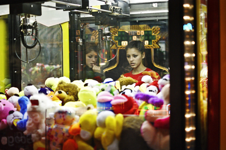 control panel lights: 2 teenagers are looking  inside the crane machine Stock Photo