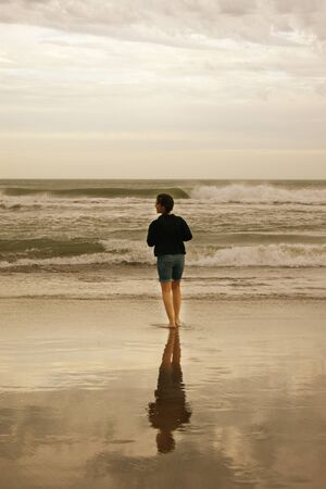 mirro: Girl standing at edge of water at a beach of Mar del Plata, Argentina with reflection of her