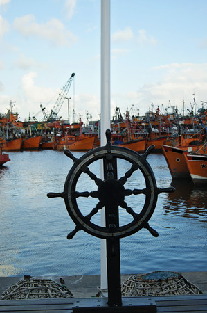 coastal city: A boat steering wheel  and typical orange fishing boats on the port of the coastal city of  Mar del Plata, Argentina. Stock Photo