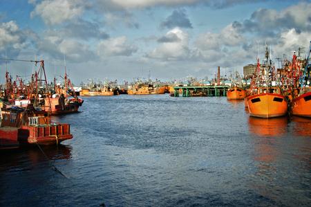 coastal city: Typical orange fishing boats on the port of the coastal city of  Mar del Plata, Argentina. Stock Photo