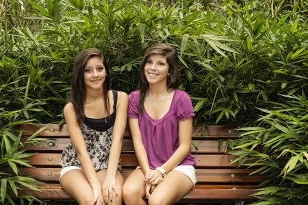 夏の日にヒューストンの美しい公園のベンチに座っている 2 人の若い女性