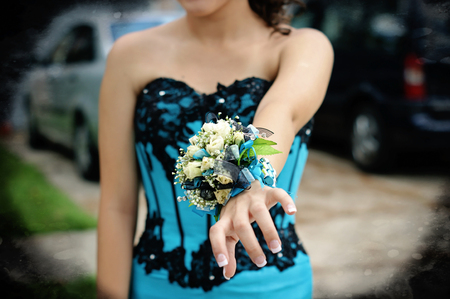corsage: Pretty turquoise and black wrist corsage worn to the prom. Stock Photo