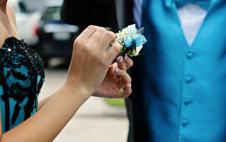 corsage: High school couple getting ready for their Senior Prom 2012.