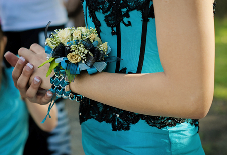 Pretty turquese and black wrist corsage worn to the prom. Stock Photo