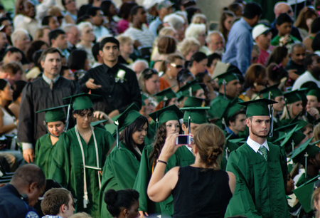Houston, USA - June 10, 2012: Wearing caps and gowns, graduating high school seniors wait their turn to receive diplomas during Spring Highschool ceremony 2012 in Houston, TX Editorial