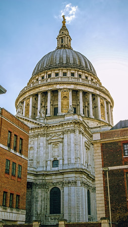 View of St Pauls cathedral from between neighbouring buildings in London.