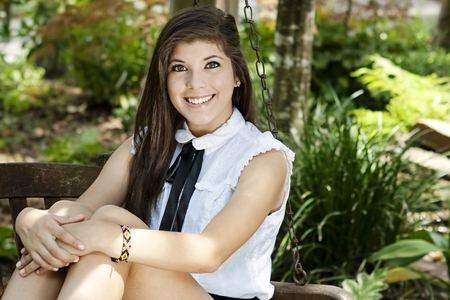 High School Graduate poses in a park for her graduation pictures