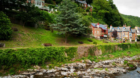 lyn: A row of houses offering bed and breakfast accommodation alongside the East Lyn River in Lynmouth in North Devon England UK