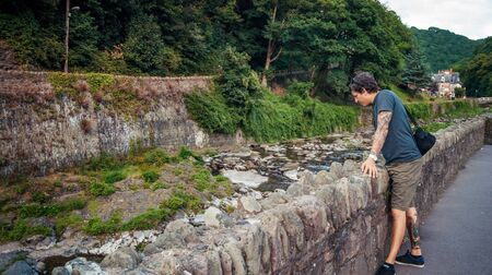 lynmouth: man looking by the East Lyn River in Lynmouth ,North Devon England UK Stock Photo