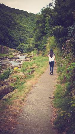 lynmouth: girl walking in Glen Lyn Gorge,  in Lynmouth in North Devon England UK