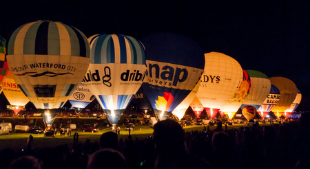 Bristol, UK - August 13, 2016: A row of Hot Air Balloons glow at night for the Bristol Balloon Fiesta at Ashton Court Editorial
