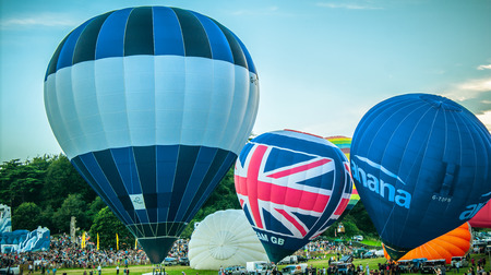 Bristol, UK - August 13, 2016: The Bristol International Balloon Fiesta 2016, showing the mass ascent and landings of over 100 balloons including special shapes and the night glow, where the burners are used at night to illuminate the balloons. This ann Editorial