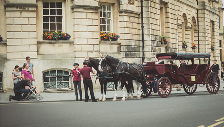 Bath Spa,UK-July 4,  2015: Two horses ready to pull a carriage full of tourists around the beautiful city of Bath on a sunny day. This is  a fun way to see the city.