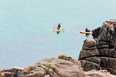 Porthcurno, Cornwall, England - July 24, 2018: People kayaking in Rocks and Sea at Porthcurno, Cornwall, beneath the Minack Open Air Theatre, Cornwall, England, UK