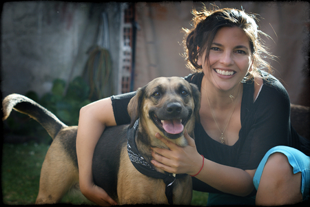 Portrait of smiling, cheerful woman holding her pet dog. A Black, active mix lab. Reklamní fotografie