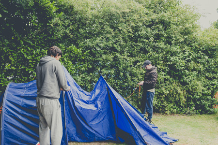 Campers setting  up a nylon tent in a Camping holidays close to Bristol, England. 版權商用圖片