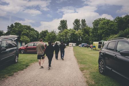 Bristol, Uk - July 16, 2017: family walking trough cars parked on a grassy campground Editorial