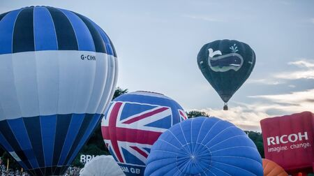 Bristol, UK - August 13, 2016: The Bristol International Balloon Fiesta 2016, showing the mass ascent and landings of over 100 balloons including special shapes and the 'night glow', where the burners are used at night to illuminate the balloons. This ann