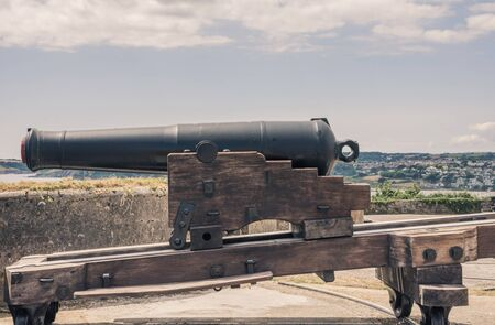 Falmouth, Cornwall, England - July 25, 2018:  Big gun at Pendennis Castle in Cornwall, England. Pendennis castle was first commissioned by King Henry VIII in response to invasion threats from the cont