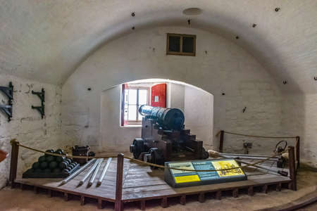 26 July 2018 - Dartmouth, Devon, UK: A black cannon sits peacefully on a wooden gun carriage facing a gun port closed by a window in the tower of Dartmouth Castle