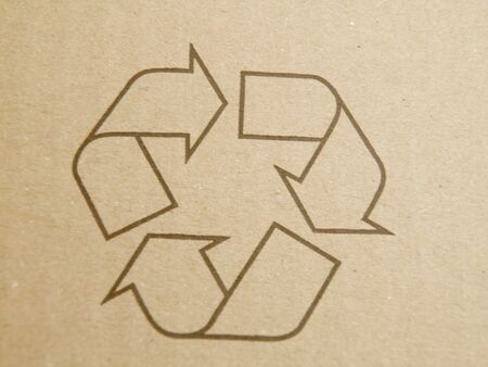 Brown corrugated cardboard sheet with recycling symbol photo