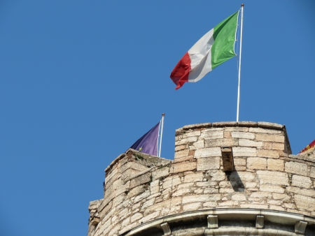 Italian flag on the top of an old tower photo