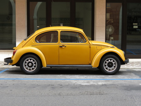 TREVISO, ITALY - CIRCA JULY 2014: Yellow Beetle vintage car parked in a street of the city centre.