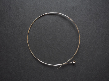 Brand new nickel folk or elctric guitar string. G-string 0.016, isolated on black.