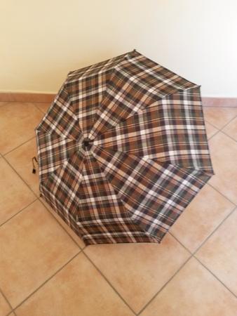 brolly: Paraguas tart�n abierta sobre baldosas de ladrillo rojo