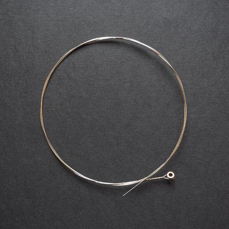 gstring: Brand new nickel folk or elctric guitar string. G-string 0.016, isolated on black.