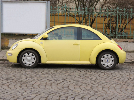 PRAGUE, CZECH REPUBLIC - CIRCA MARCH 2015: Yellow Volkswagen New Beetle car parked in a street of the city centre. 新聞圖片