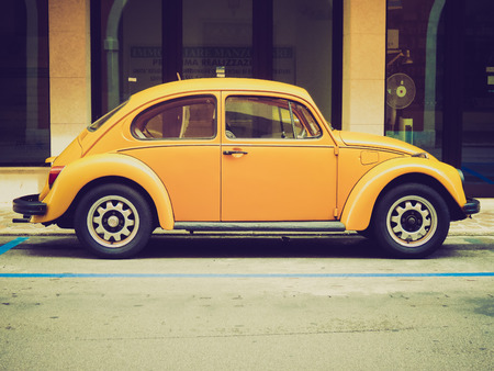 TREVISO, ITALY - CIRCA JULY 2014: Yellow Volkswagen Beetle vintage car parked in a street of the city centre. 新聞圖片