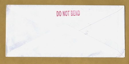 bend over: do not bend - paper envelope over light brown background