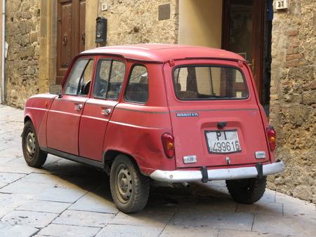 red centre: VOLTERRA, ITALY - CIRCA DECEMBER 2014: A red Renault 4 parked in the old city centre Editorial