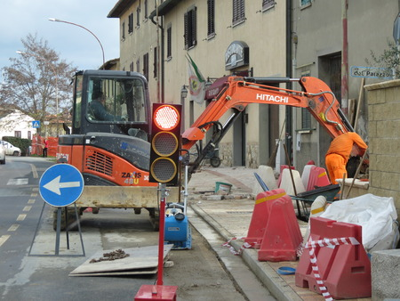 SIENA, ITALY - CIRCA DECEMBER 2014: road construction site with caterpillar, traffic signs and traffic light