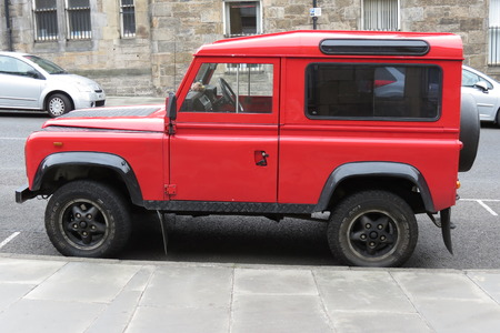 defender: EDINBURGH, UK - CIRCA AUGUST 2015: red Land Rover Defender 110 parked on a street in the city centre