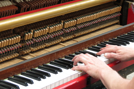 upright piano: two hands playing an upright piano