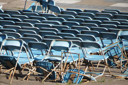 messed up: Empty audience blue plastic chairs messed up
